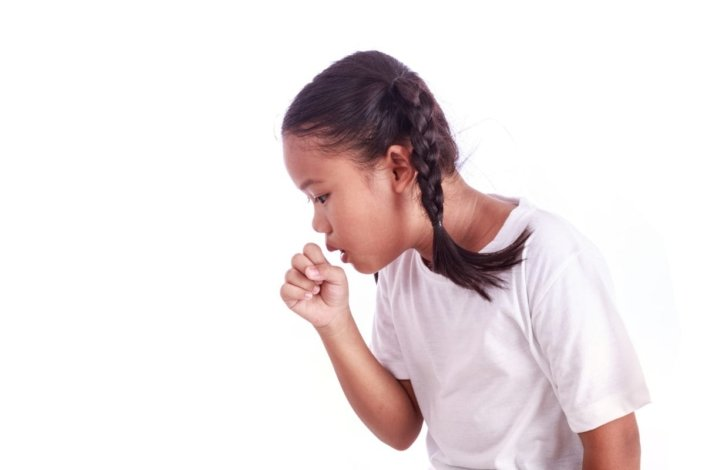 Young girl coughing into her hand.