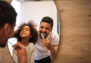 A father and daughter brushing their teeth together