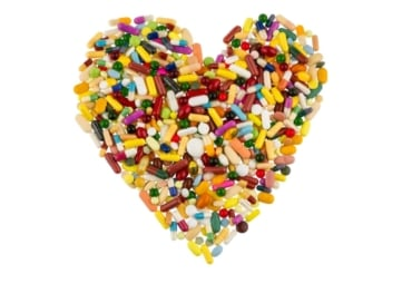 Colorful tablets and capsules arranged in heart shape to represent medicine for heart problems