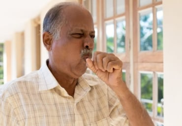 Close-up of man coughing, covering his mouth with his hand
