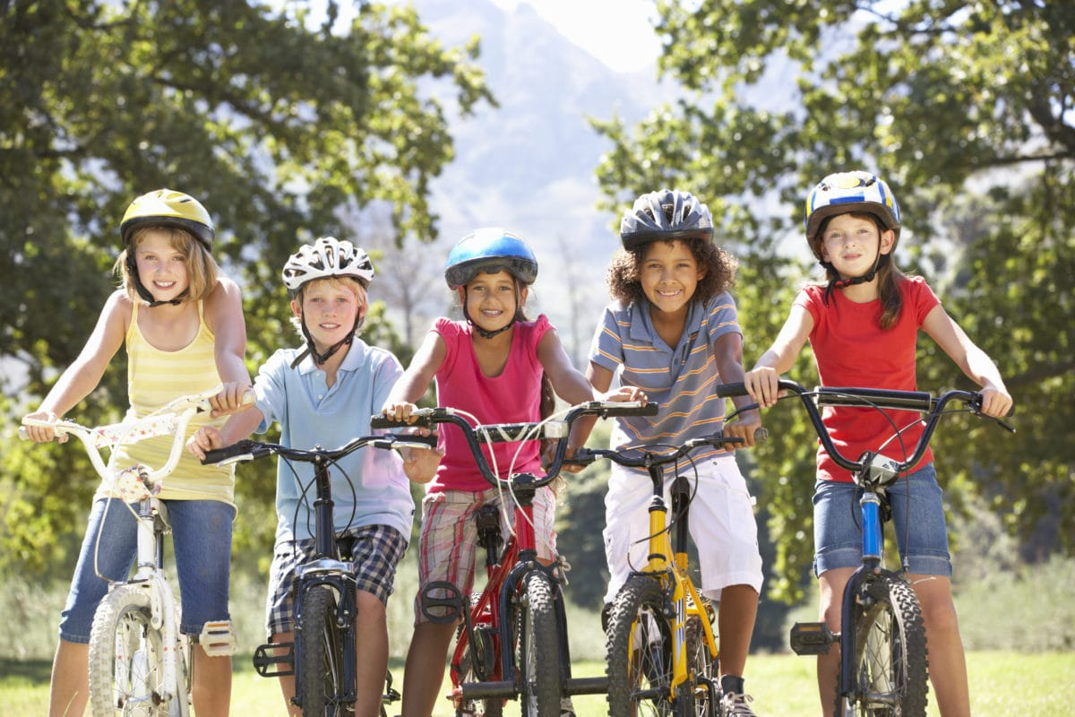 Smiling group of children on bikes and wearing helmets in the park