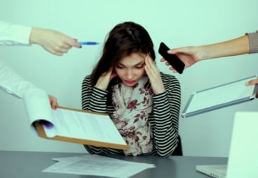 Woman holding head, showing stress while many things are being handed to her
