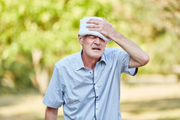 Senior man with heatstroke cools his head with a wet cloth