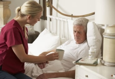 Nurse providing care to elderly man at home in bed