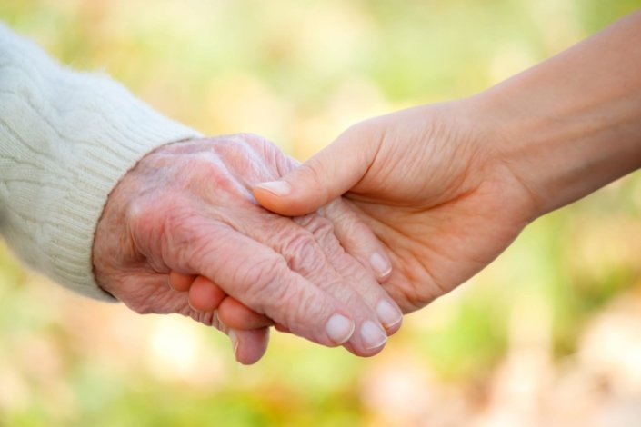 a senior holding hands with a caregiver