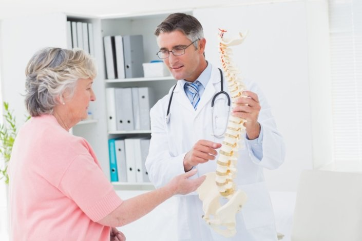 doctor and senior female patient look at a model of a spine