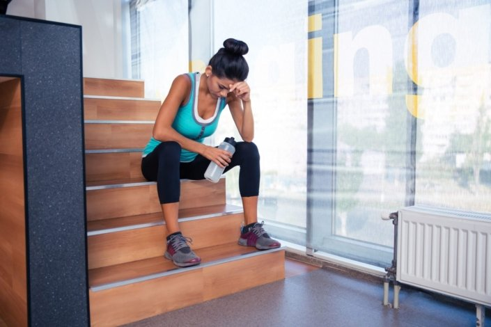 Tired woman sitting on the stairs with bottle of water in gym