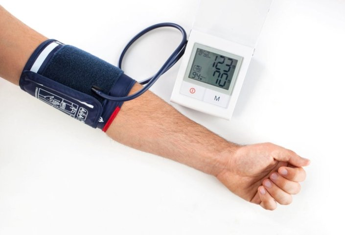 man wearing blood pressure monitor on arm