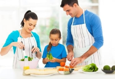 Parents and young child prepare healthy meal together in kitchen