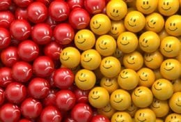 Left side showing red balls with frowning faces, right side showing yellow balls with smiley faces