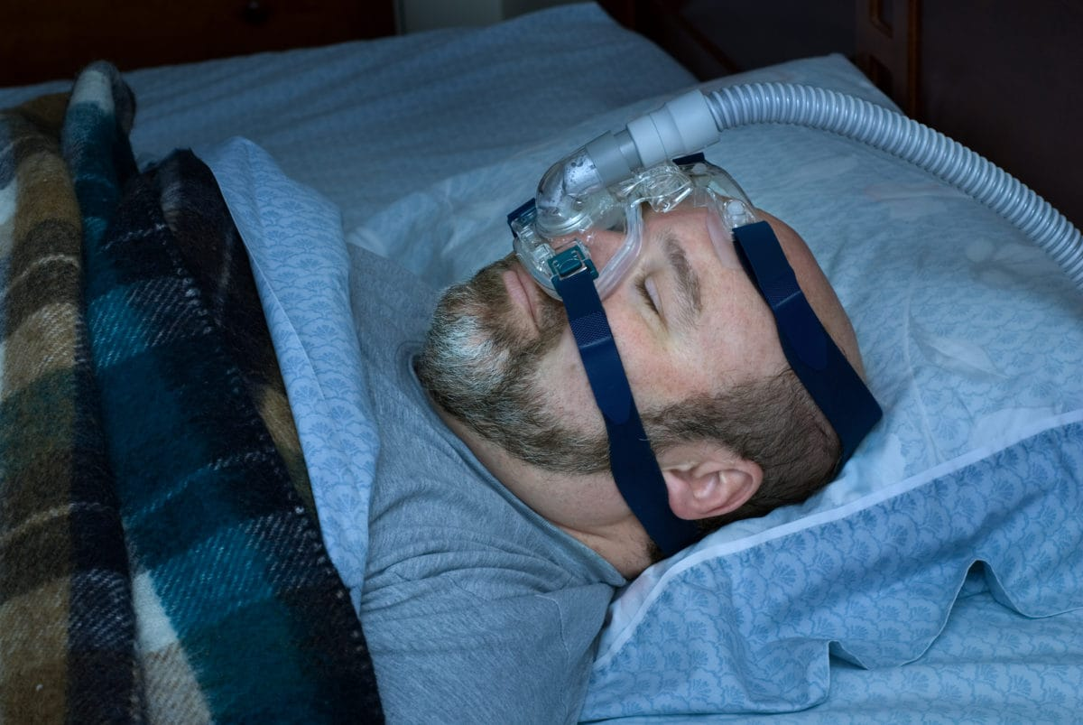 Man sleeping on back with nasal mask.