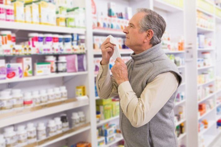 sick man holding tissue looks at OTC medicines in a pharmacy