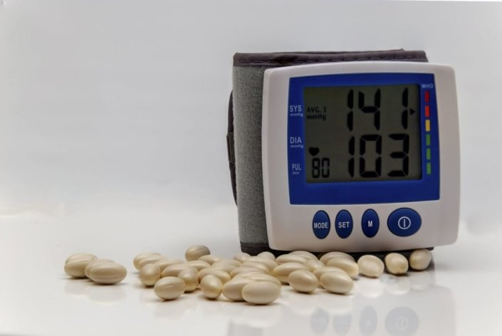 blood pressure monitor showing elevated readings with pills on a table