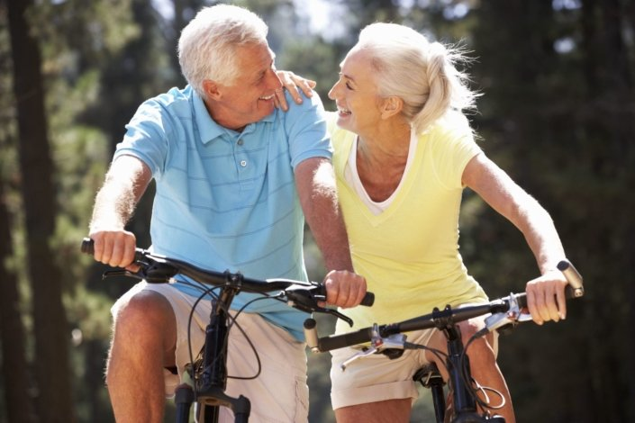 A older couple biking together outdoors