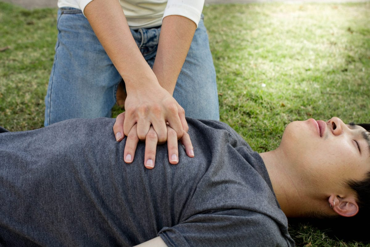 Young man lying on grass while female bends over him doing CPR