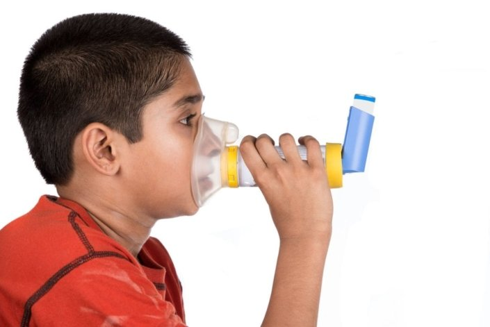 young boy using spacer and mask with asthma inhaler