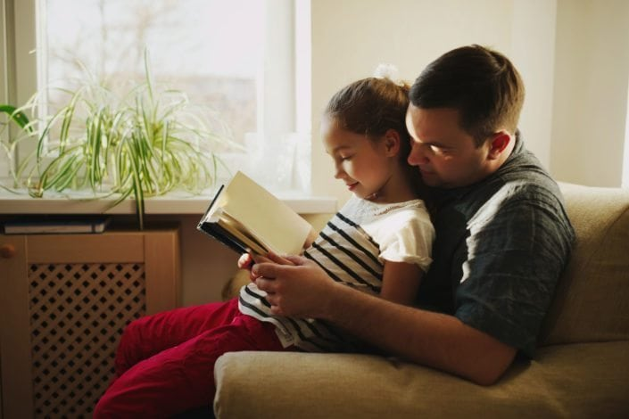father and daughter sitting on couch reading a book together