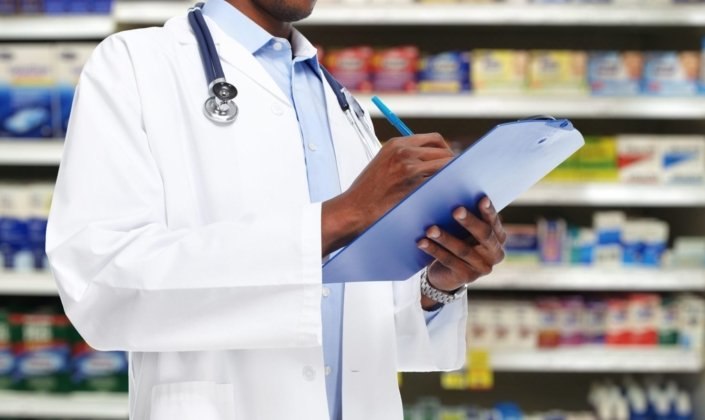 doctor writes on clipboard in front of aisle of OTC medicines