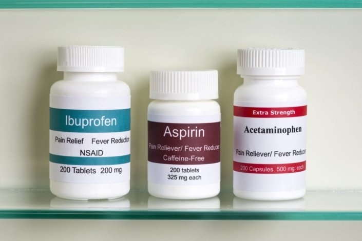 Bottles of ibuprofen, aspirin, and acetaminophen in a medicine cabinet
