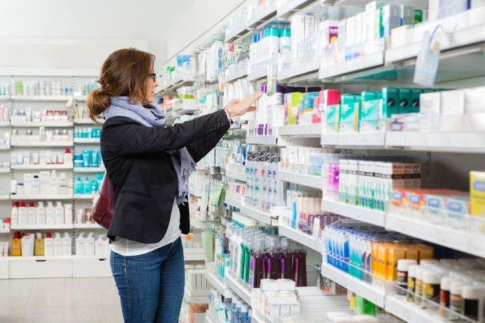A women looks for supplies in the aisle of a pharmacy