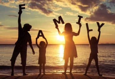 "Family standing on the beach at sunset, holding letters that spell ""family"""