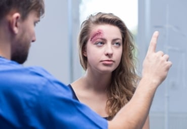 A woman with a head injury being checked by a doctor