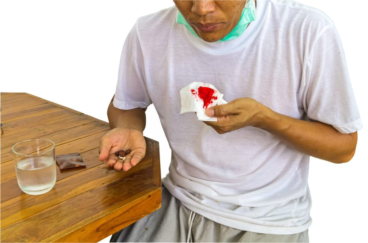 Male patient holding a bloody tissue in one hand and medicine in the other hand