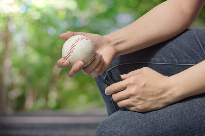 close-up of a young man in jeans holding a baseball in his hand