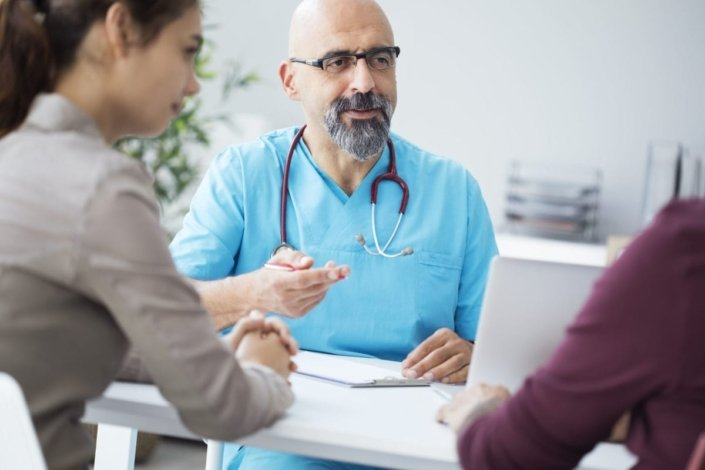 Two people talking to a doctor in the doctor's office