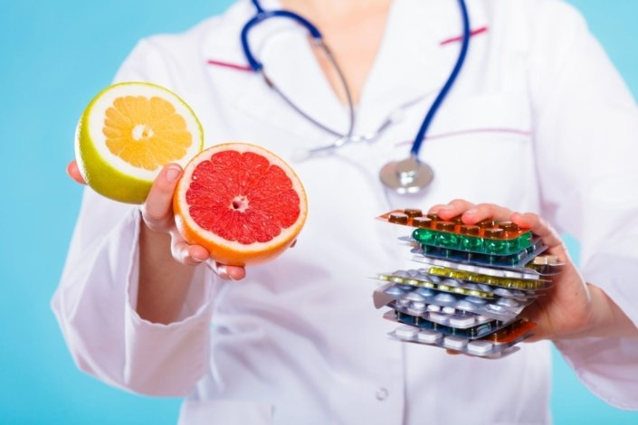 a doctor holding grapefruit in one hand and medication in the other