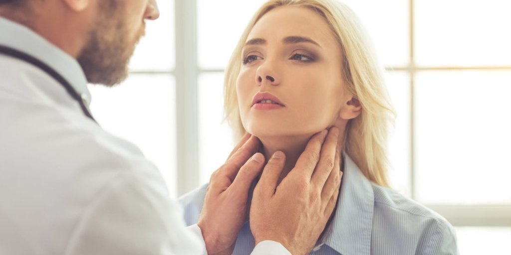 doctor examining female patient for hypothyroidism while working in his office