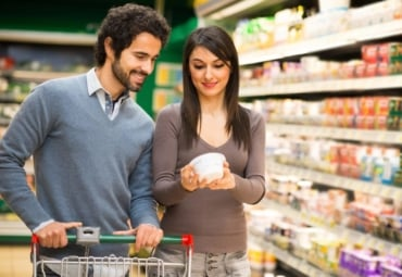 Young couple reading a nutrition label in the supermarket