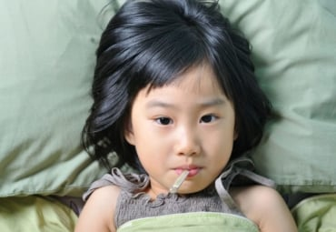 A little girl in bed with a thermometer in her mouth