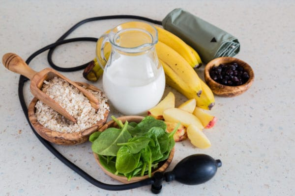 Healthy food and drink choices on table surrounded by blood pressure monitor