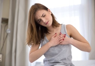 A woman having chest pains, with her hands over her heart