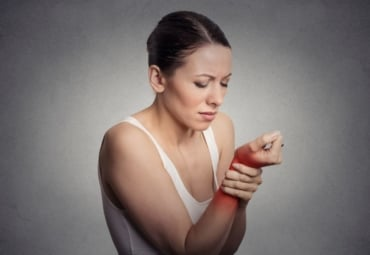 Woman holds her wrist in pain