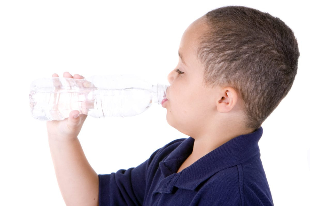Boy drinking from water bottle on white background