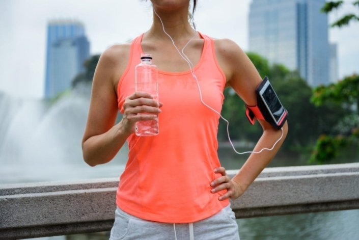 A sweaty woman dressed in workout clothes standing outside in the city holding a bottle of water
