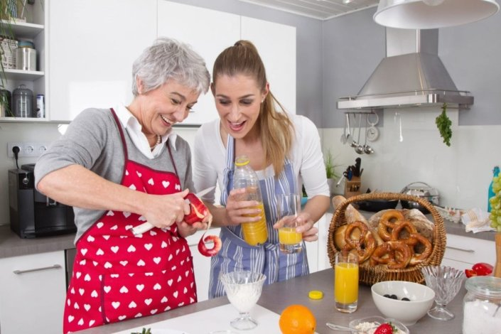 Senior mother and daughter making healthy breakfast together in kitchen.