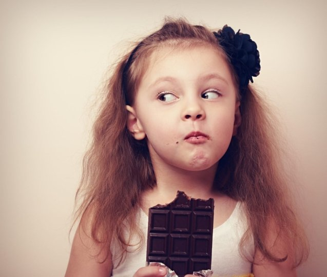 Girl eating large chocolate bar and looking to see if anyone is watching