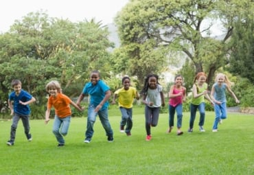 Group of children racing each other in the park