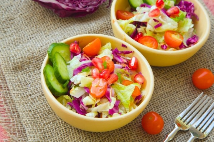 Two bowls of healthy salad on table with forks