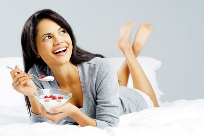 Woman smiling and eating yogurt with berries