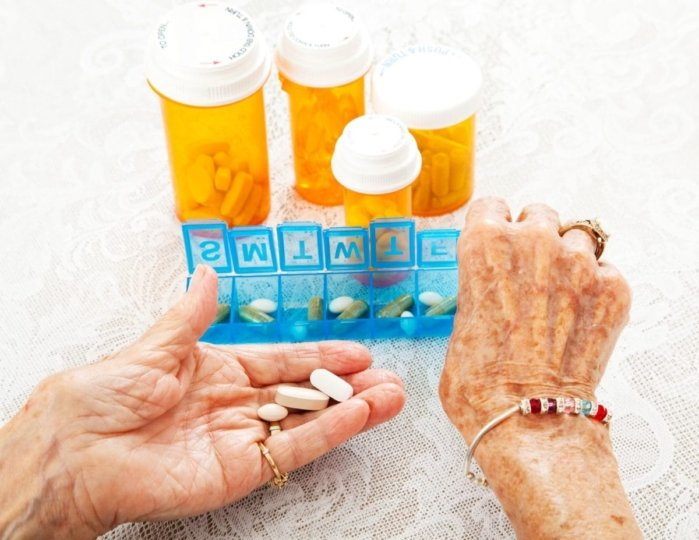 Closeup of elderly woman's hands sorting several prescriptions