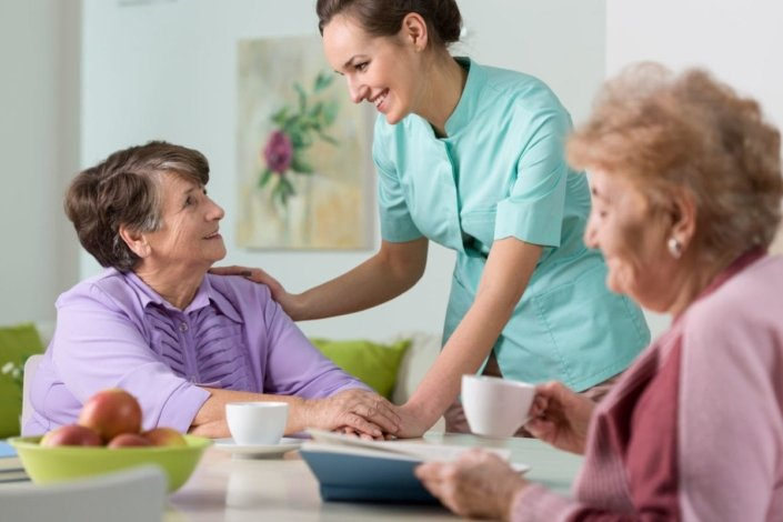 Two older women visiting with nurse in nursing home