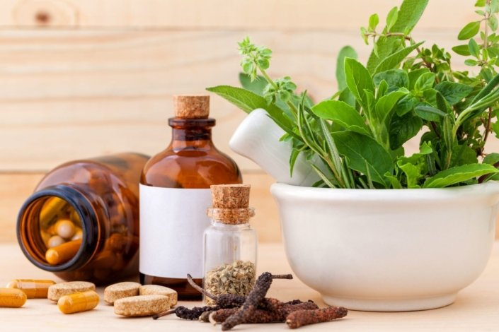 bowl of fresh herbs, plus dried herbs and capsules on a table