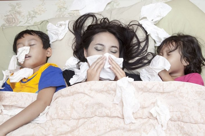 A mother and two young children lie in bed blowing their noses