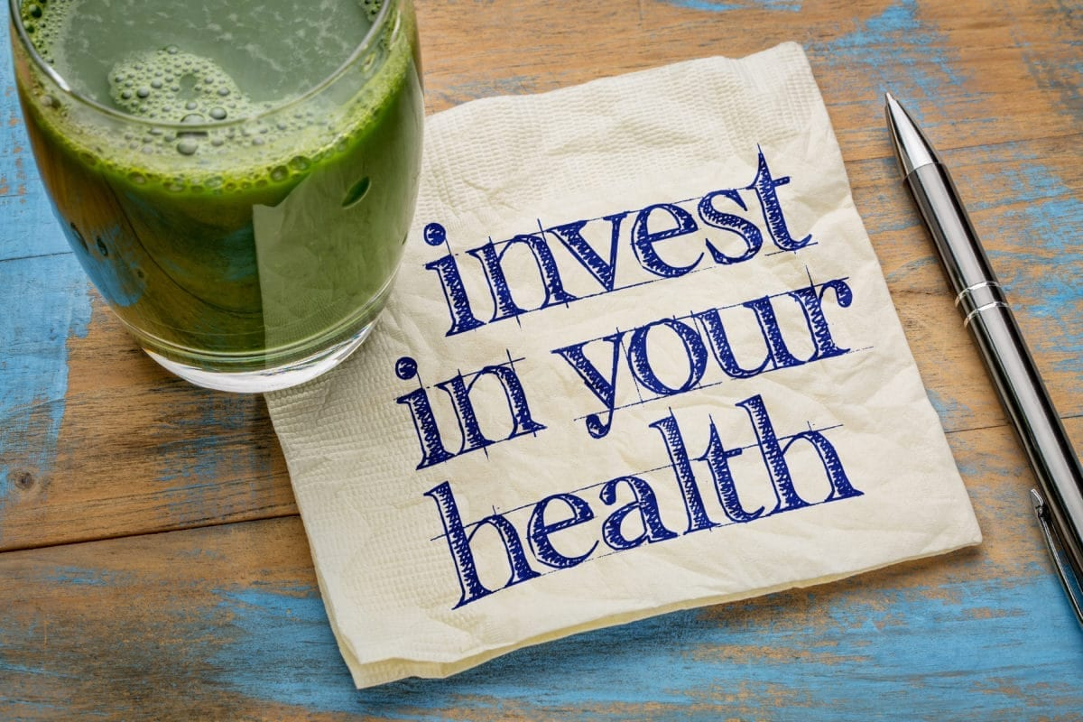 invest in your health advice or reminder - handwriting on a napkin with a glass of fresh, green, vegetable juice