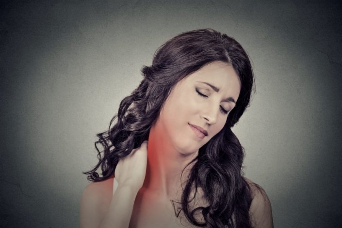 Young woman massaging neck, which is in pain