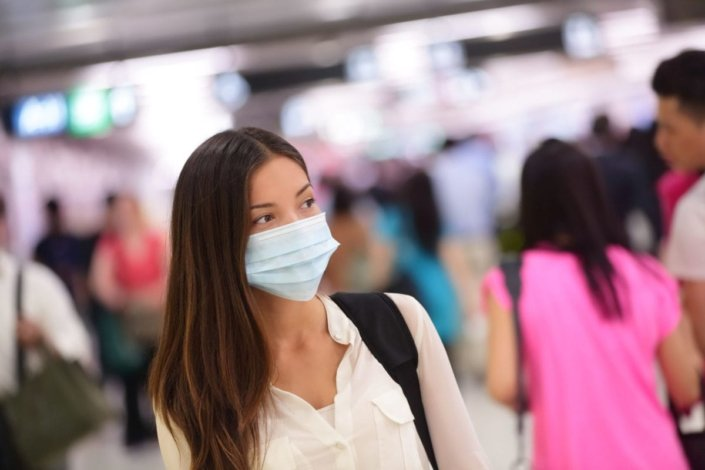 Young woman wearing a mask to protect from getting H1N1 influenza